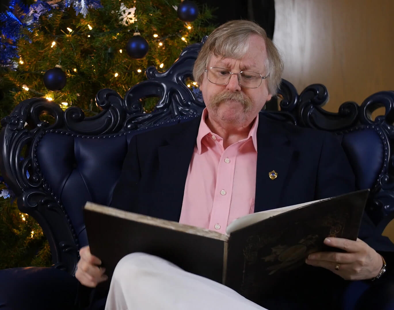 professor phillips reading in front of a christmas tree